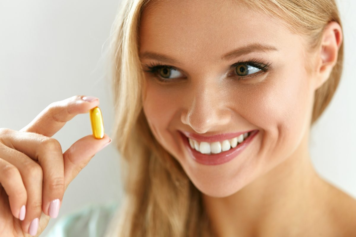 Blonde woman taking a nutritional supplement or vitamin